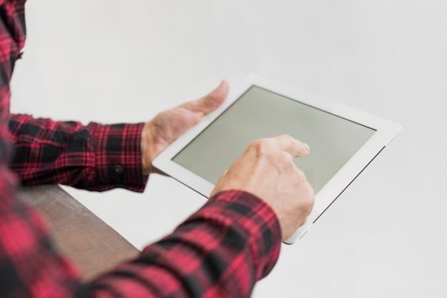 Reifer mann des hohen winkels, der auf seiner tablette schaut
