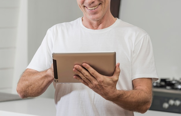 Reifer mann des smiley, der eine tablette verwendet