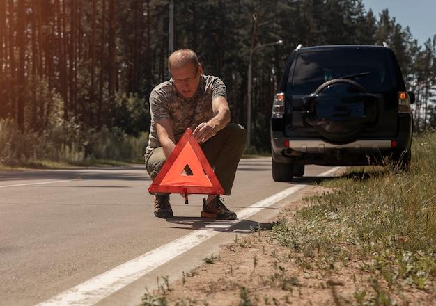 Reifer mann fahrer, der nach einem unfall dreieck vorsicht und warnschild auf asphalt in der nähe des autos setzt ...