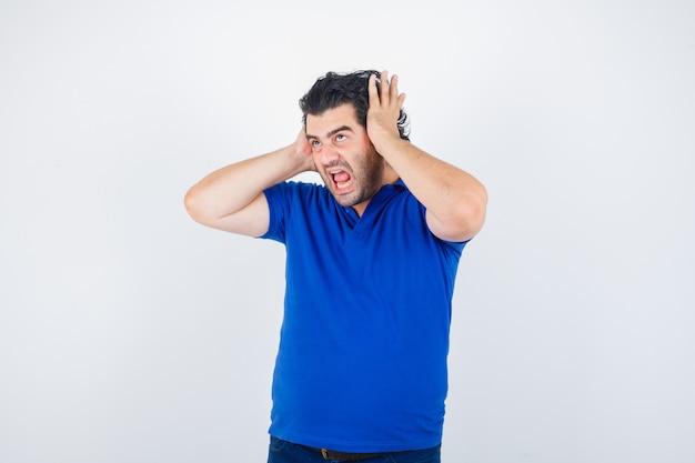 Reifer mann im blauen t-shirt, das hände auf ohren hält und aggressive vorderansicht schaut.
