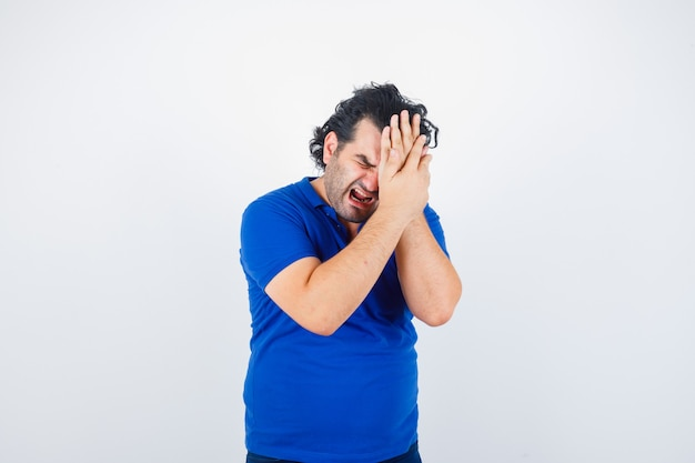 Reifer mann im blauen t-shirt, das unter migräne leidet und gereizt sieht, vorderansicht.