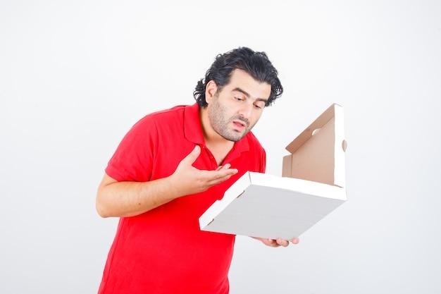 Reifer mann im roten t-shirt, das geöffnete pizzaschachtel betrachtet und hungrig schaut, vorderansicht.