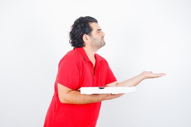 Reifer mann im roten t-shirt, das pizzaschachtel hält, während hand in fragender geste streckt und ernsthafte vorderansicht schaut.
