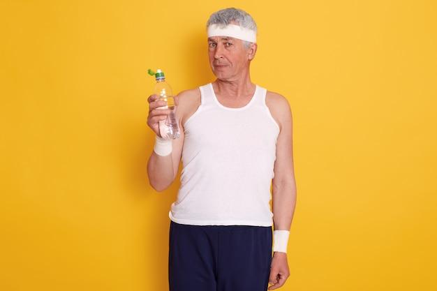 Reifer mann im stirnband und hält eine flasche wasser, ruht zwischen sportgarnituren, trägt t-shirt und hose