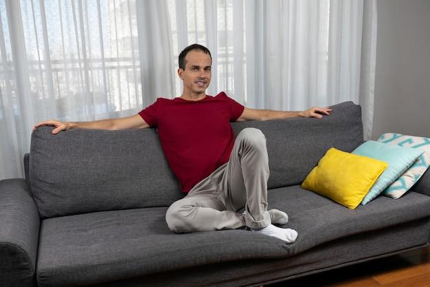 Reifer mann jahre alt sitzt auf dem sofa mit offenen armen neben bunten kissen.