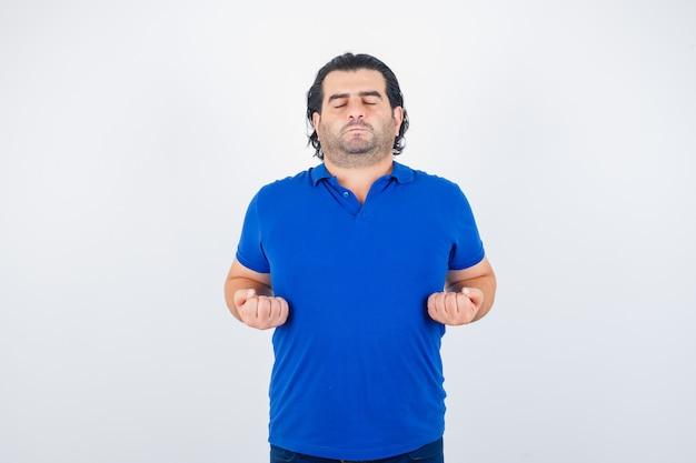Reifer mann meditiert, hält die augen in blauem t-shirt, jeans geschlossen und sieht ruhig aus, vorderansicht.
