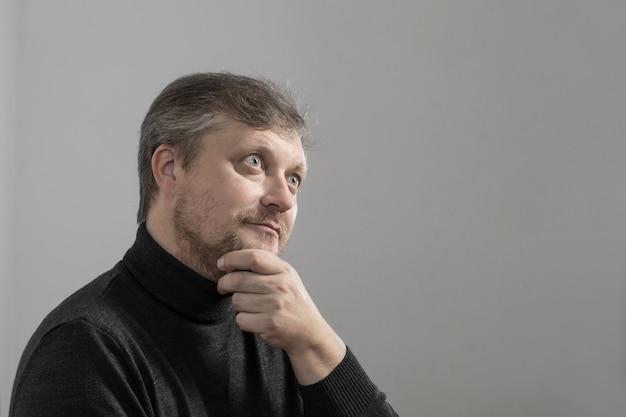 Reifer mann mit bart auf grauer oberfläche
