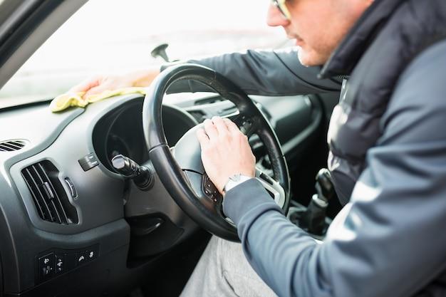 Reifer mann mit brille, die das armaturenbrett des autos mit einem gelben tuch säubert.