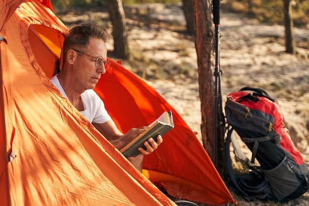 Reifer mann mit brille entspannt sich mit literatur im zelt nach nordic walking im sonnigen wald
