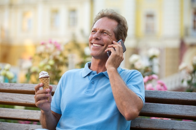 Reifer mann mit dem telefonlächeln.