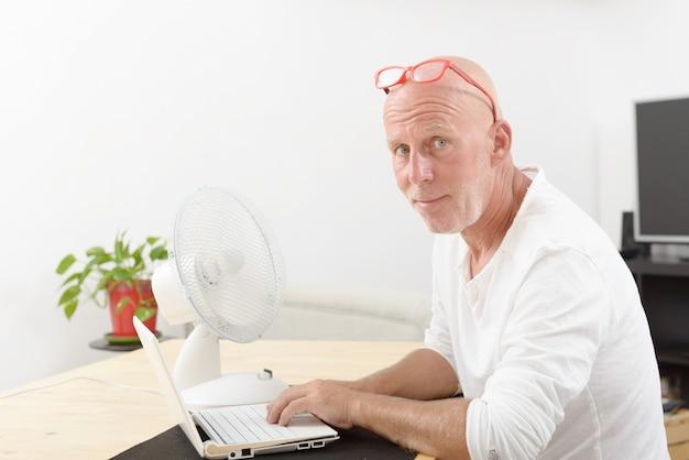 Reifer mann mit einem laptop im haus