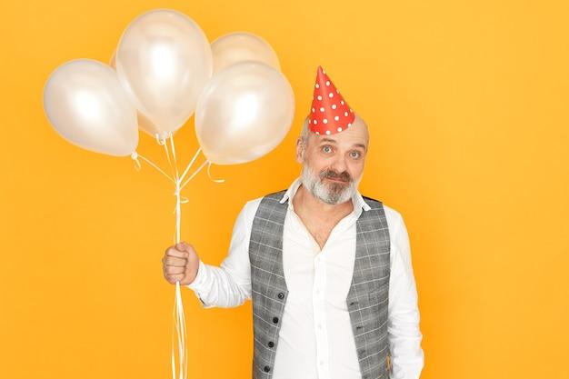 Reifer mann mit grauem bart, der jahrestag feiert. porträt des schönen unrasierten männlichen rentners, der heliumballons hält, die spaß an der geburtstagsfeier haben.
