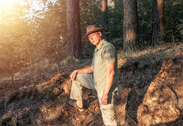 Reifer mann mit hut, der im sommerwald mit bäumen und sonnenlicht spazieren geht, der für die kamera posiert, niedliche männliche wandern