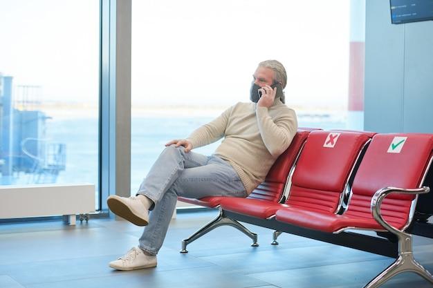 Reifer mann mit maske, der während der pandemie auf einem stuhl sitzt und im wartezimmer des flughafens telefoniert