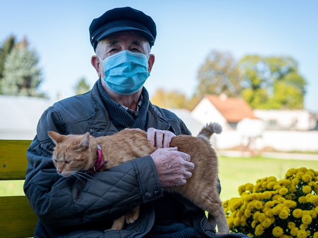 Reifer mann mit maske, die katze hält