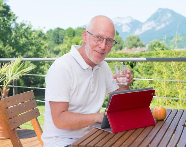 Reifer mann mit tablette auf der terrasse, trinkwasser