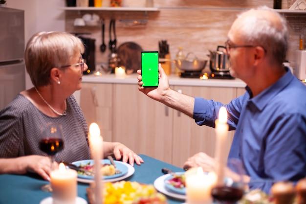 Reifer mann mit telefon mit grünem bildschirm in der küche während eines romantischen abendessens mit frau. ältere menschen, die sich die chroma-key-mockup-vorlage ansehen, isolierte smartphone-anzeige mit technologie-internet.