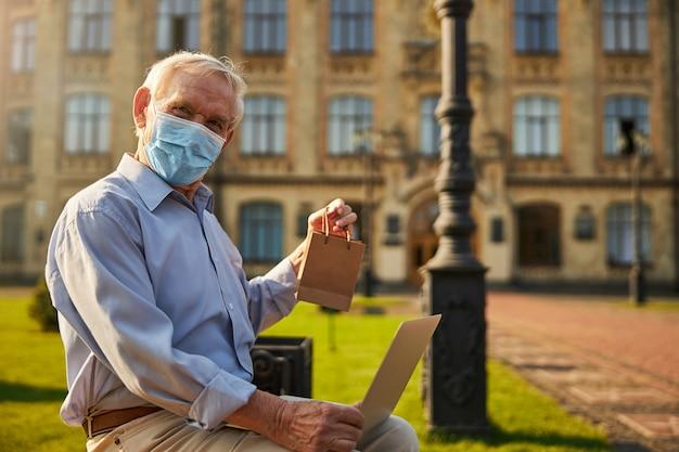 Reifer mann mit tragbarem computer in der nähe von pflegeheim