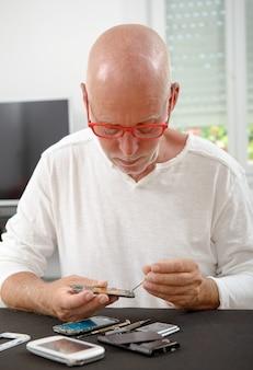Reifer mann reparierte ein smartphone