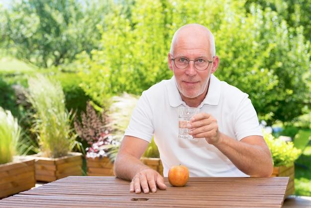 Reifer mann trinkt ein glas wasser auf der terrasse