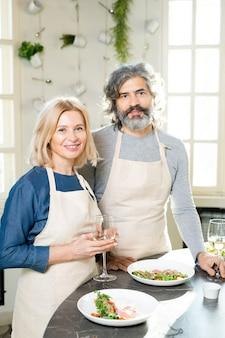 Reifer mann und frau in schürzen, die am küchentisch stehen, serviert mit appetitlichen hausgemachten speisen auf tellern und weißwein in flöten