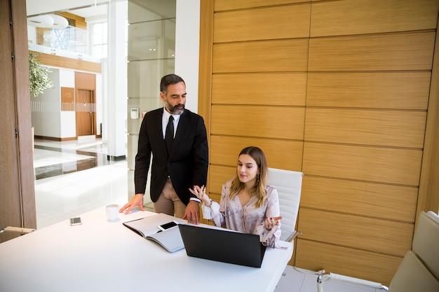 Reifer mann und junge frau geschäftspartner mit laptop arbeiten im büro