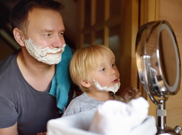Reifer mann und kleiner junge, die spaß mit schaum beim zusammen rasieren hat. der kleine sohn ahmt seinen vater nach.