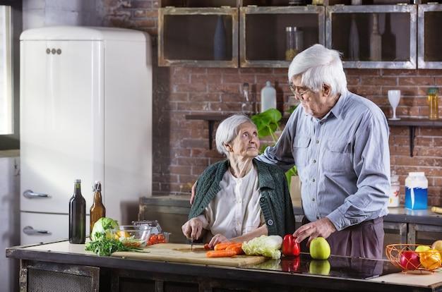 Reifer mann und seine mutter kochen zusammen. älteres paar, das mahlzeit in der küche vorbereitet. frau hackt gemüse.