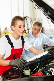 Reifer mann und weiblicher automechaniker in der werkstatt