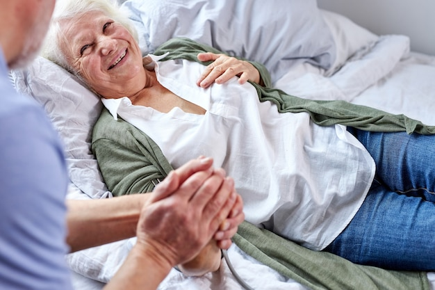Reifer mann unterstützt seine kranke frau auf dem bett liegend, frau leidet unter hohem druck, weibliches lächeln