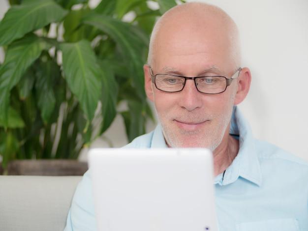 Reifer mann zu hause, der auf internet websurfing ist