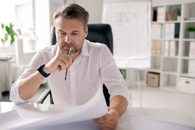 Reifer nachdenklicher ingenieur mit bleistift und papier, die skizze betrachten, während an ideen durch arbeitsplatz im büro denken