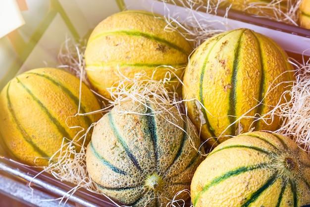 Reifer neuer melonenkasten auf einem landwirtmarkt. tiefenschärfe mit sonnenlicht.