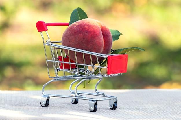 Reifer pfirsich in einem einkaufswagen auf unscharfem hintergrund