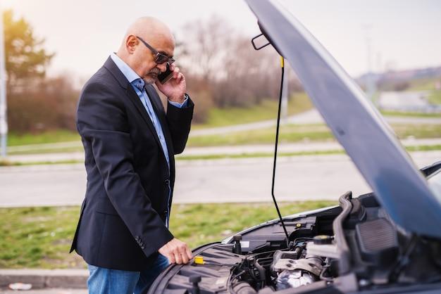 Reifer professioneller eleganter gestresster geschäftsmann im anzug schaut unter die motorhaube und ruft abschleppwagen an.