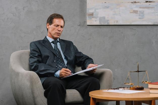 Reifer rechtsanwalt, der auf lehnsessel schreibt auf klemmbrett im gerichtssaal sitzt