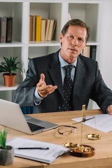 Reifer rechtsanwalt, der im gerichtssitzungsgestikulieren sitzt