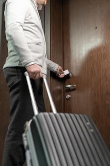 Reifer reisender mit kofferöffnungstür des hotelzimmers