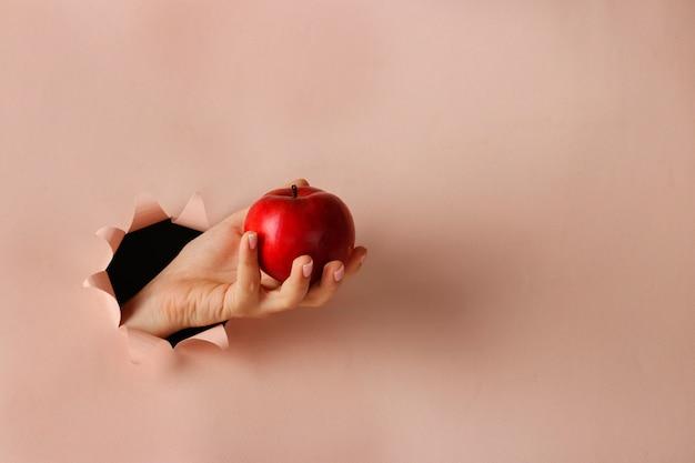Reifer roter apfel in einer weiblichen hand durch rundes loch in rosa papier