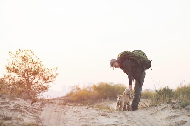 Reifer rucksacktourist bückt sich für hund