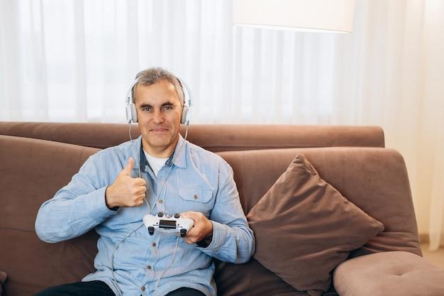 Reifer spielermann, der videospiel mit joystick und kopfhörern spielt, glücklich mit großem lächeln, daumen hoch. ausgezeichnetes zeichen. wohnzimmer im hintergrund. mann in freizeitkleidung.