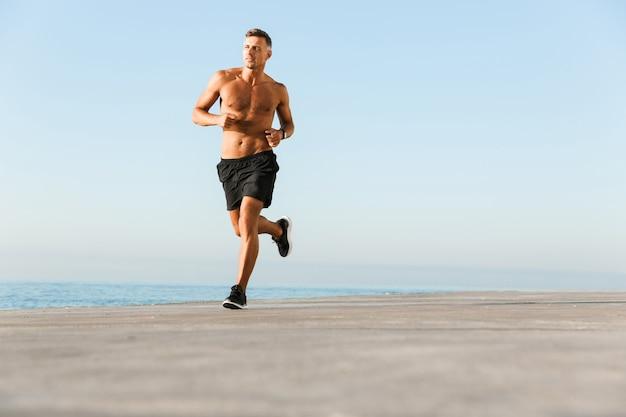 Reifer sportler, der draußen am strand läuft.