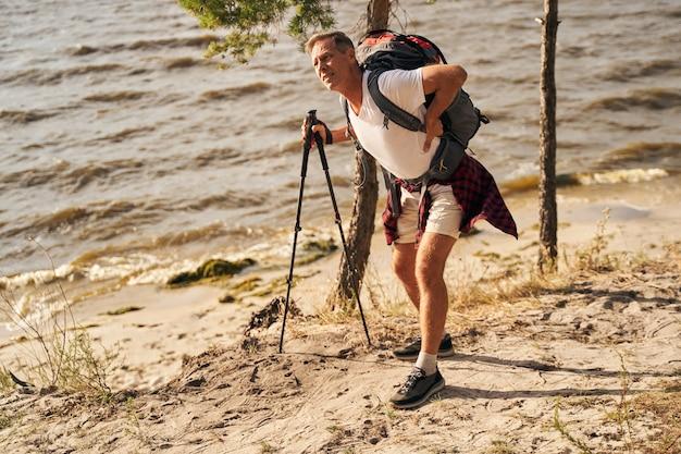 Reifer sportlicher mann geht nordic walking in der nähe der küste und leidet unterwegs unter schmerzen im unteren rückenback