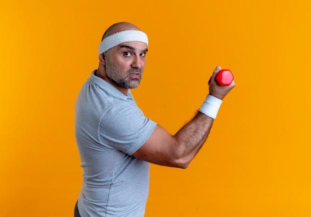 Reifer sportlicher mann im stirnband, der angespannt und selbstbewusst mit hanteln über orange wand arbeitend aussieht