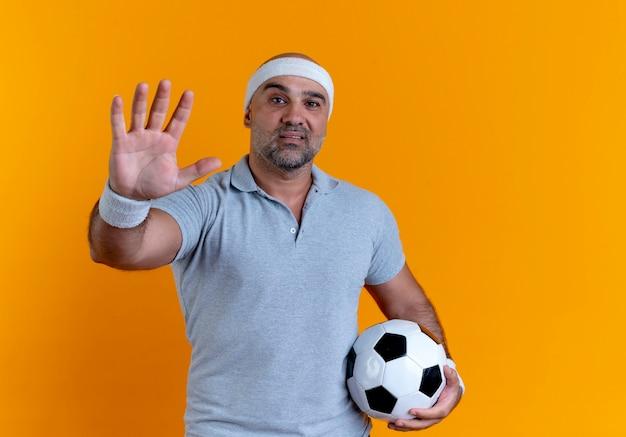 Reifer sportlicher mann im stirnband, der fußball hält, der nach vorne schaut und handfläche zeigt, die über orange wand steht