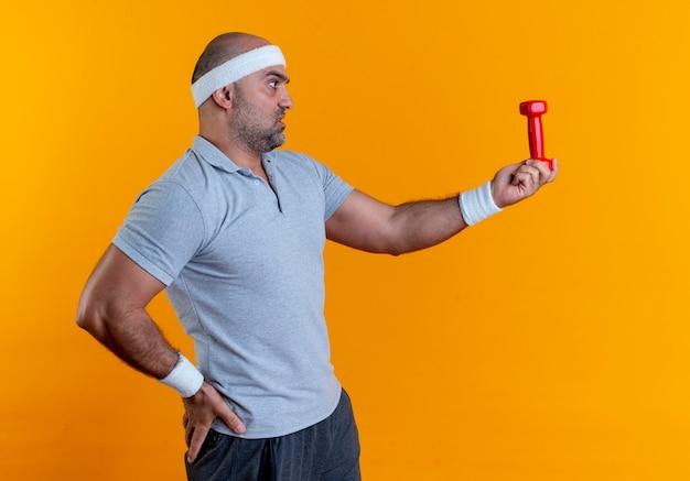 Reifer sportlicher mann im stirnband, der hantel hält, der es mit ernstem gesicht betrachtet, das über orange wand steht