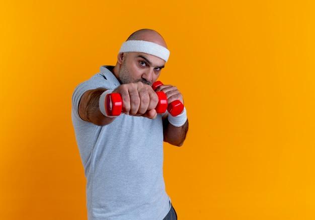Reifer sportlicher mann im stirnband, der mit hanteln arbeitet, die angespannt und selbstbewusst über orange wand 6 stehen