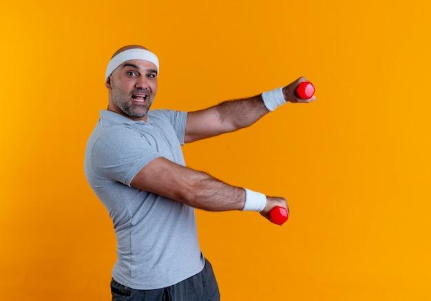 Reifer sportlicher mann im stirnband, der mit hanteln arbeitet, die sicher lächelnd über orange wand stehen