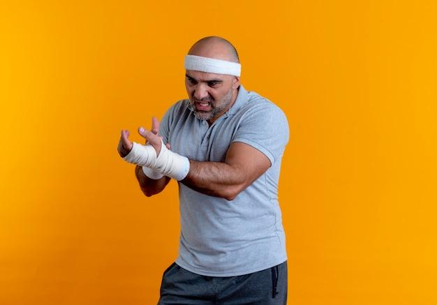 Reifer sportlicher mann im stirnband, der seine bandagierte hand berührt und unwohl aussieht und unter schmerzen leidet, die über der orangefarbenen wand stehen