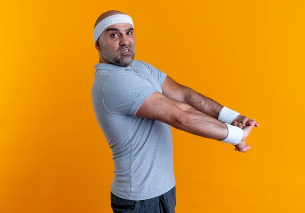 Reifer sportlicher mann im stirnband, der seine hände ausdehnt und sicher steht, über orange wand stehend